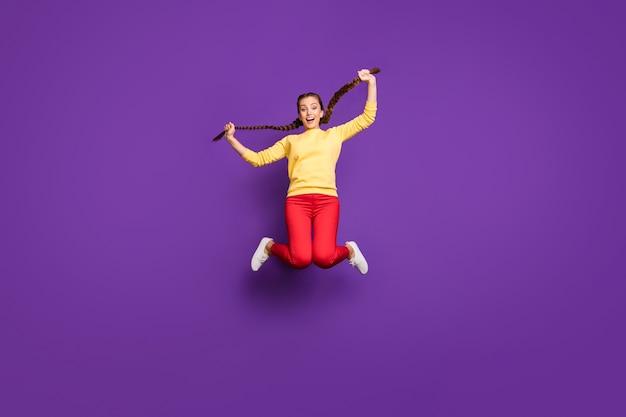 Сумасшедшая молодая дама всего тела прыгает высоко, держа в руках длинные косы, в повседневном желтом пуловере, красные брюки, изолированные на стене фиолетового цвета
