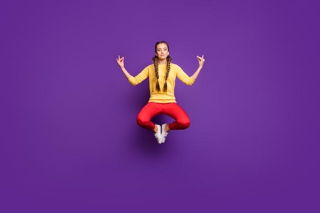 Сумасшедшая юная леди всего тела, прыгающая высоко в позе лотоса, расслабляющая тренировочная одежда для йоги, повседневный желтый пуловер, красные брюки, изолированные на стене фиолетового цвета