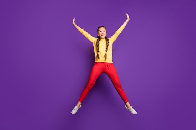 Сумасшедшая молодая дама всего тела прыгает высоко, проводя лучшее свободное время, раздвинув руки, в форме звезды, повседневный желтый пуловер, красные брюки, изолированные на стене фиолетового цвета
