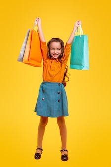 Full body delighted little girl in stylish casual clothes holding bunch of multicolored shopping bags, while representing fashion and shopping concept