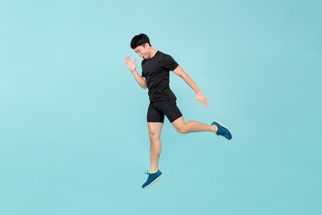 Full body of energetic young athlete asian man jumping
