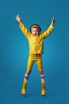 Возбужденная девочка всего тела в желтом плаще и сапогах улыбается и прыгает