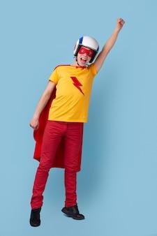 スーパーヒーローのマントとヘルメットで腕を上げ、青い背景に向かって飛ぶふりをしながら叫んでいる若い男を全身興奮させた