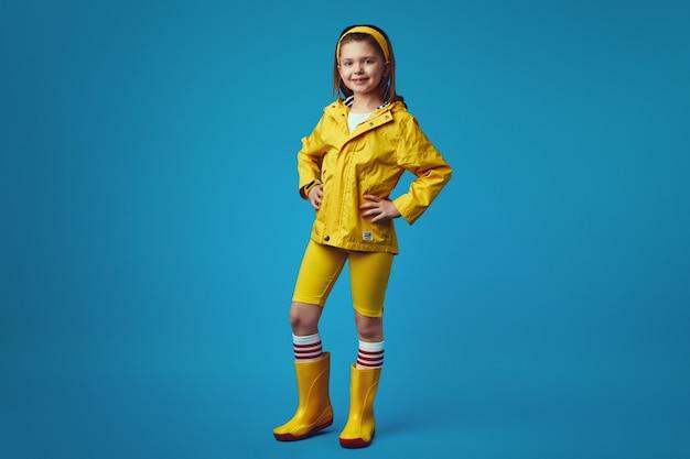 Полная девушка в желтом плаще и сапогах улыбается и держит руки на талии