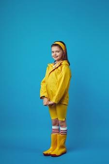 Полная девушка в желтом плаще и сапогах улыбается и держит руки вместе