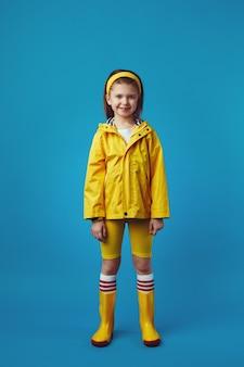 Девушка в полный рост в желтом плаще и сапогах улыбается, стоя над синим