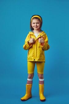Девушка в полный рост в желтом плаще и сапогах улыбается и показывает палец вверх