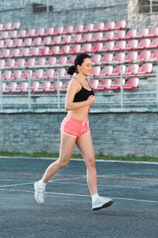 Full body of girl running track on stadium. profile of young woman in black top, pink shorts and white sneakers. outdoors, sport