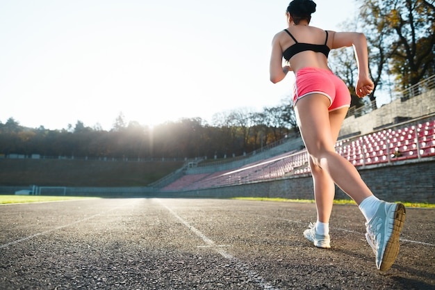 Full body of girl running track on stadium. rear view of young woman in black top, pink shorts and white sneakers. outdoors, sport, without face