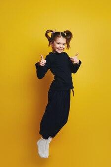 Девушка всего тела улыбается и показывает палец вверх обеими руками во время прыжка