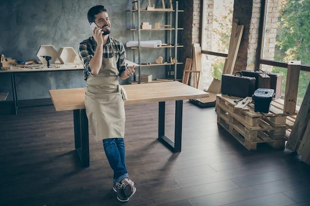 Полное тело красивый парень мастер отвечает на звонок клиента слушает новый порядок дружелюбный внимательный мастер собственный деревянный бизнес столярный цех гараж в помещении
