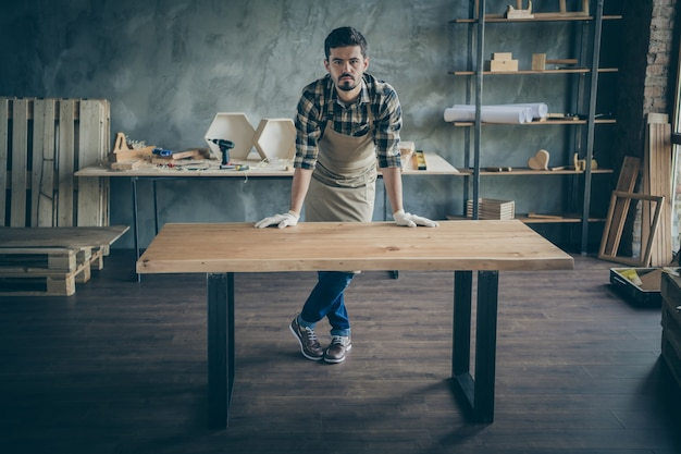 Full body  handsome guy master leaning hands on handmade slab table advertising good work selling website own wooden business industry woodwork shop garage indoors