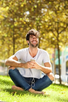 Full body happy man sitting in grass listening to music