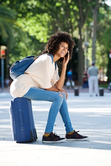 Full body happy traveler sitting on suitcase talking on smart phone