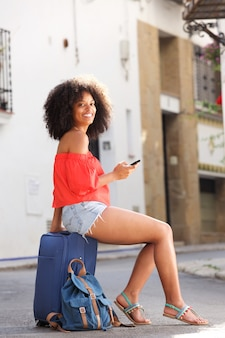 Full body happy woman sitting on suitcase with cellphone