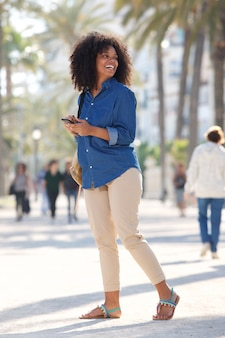 Full body happy woman walking outside with smart phone