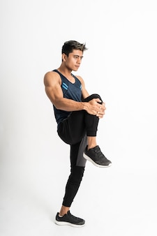 Full body image of muscle man wearing sportswear stands facing side do leg stretch by lifting the leg up in front of the stomach