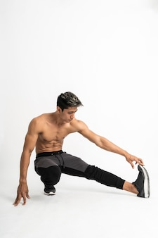 Full body image of muscle man without clothes do leg stretching by squat one leg pulled forward