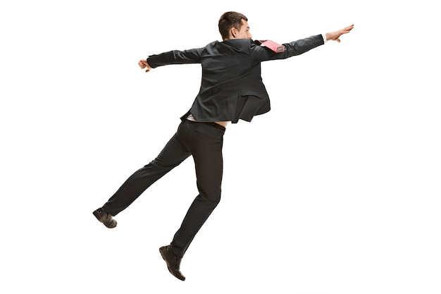 Full body jumping businessman or diplomat on white studio background. serious young man in suit, red tie in jump in office.