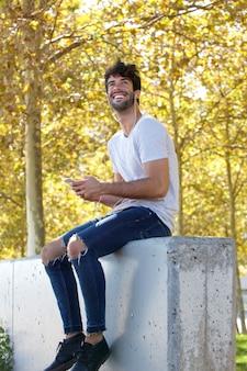 携帯電話とヘッドフォンで木々に座っている全身笑い男