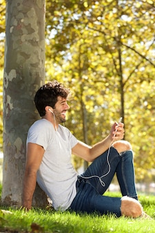 Full body laughing man sitting outside with cellphone and headphones