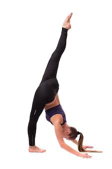 Портрет женщины-спортсмена в полный рост, растягивая ногу во время разминки, изолирован на белом фоне
