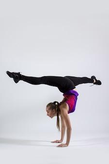 Atleta della donna del ritratto di tutta la lunghezza del corpo che allunga la gamba durante il riscaldamento isolato su priorità bassa bianca