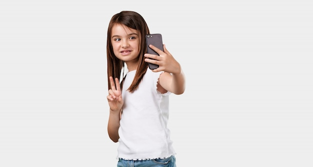 Full body little girl confident and cheerful, taking a selfie, looking at the mobile with a funny and carefree gesture, surfing the social networks and internet