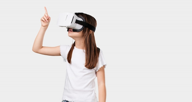 Full body little girl excited and entertained, playing with virtual reality glasses