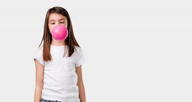 Full body little girl happy and joyful, inclosing a chewing gum balloon