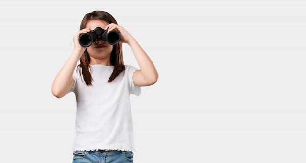 フルボディの女の子が驚きと驚き、遠くに何か双眼鏡で見て何か面白い、将来の機会の概念