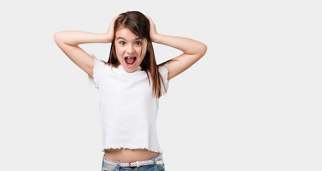 全身の小さな女の子が驚きとショックを受け、広い目で見て、オファーや新しい仕事に興奮して、コンセプトに勝つ
