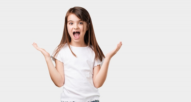 Full body little girl surprised and shocked, looking with wide eyes, excited by an offer or by a new job, win concept