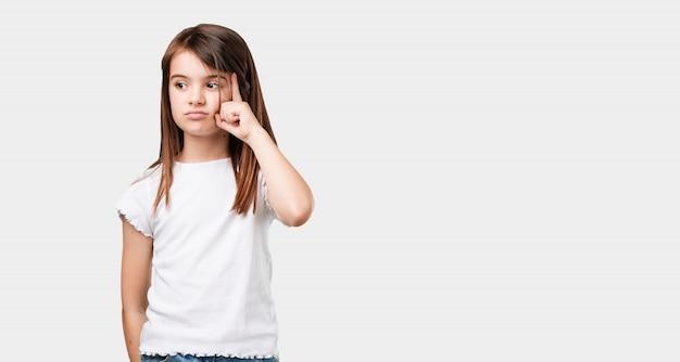 考えて見上げる、考えについて混乱している全身の小さな女の子