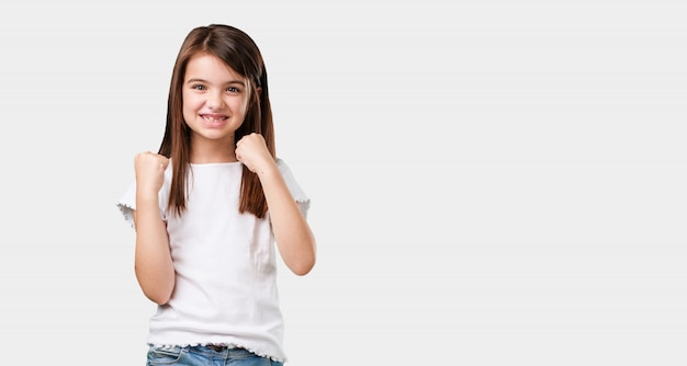 フルボディの女の子はとても幸せで興奮、腕を上げる、勝利または成功を祝う