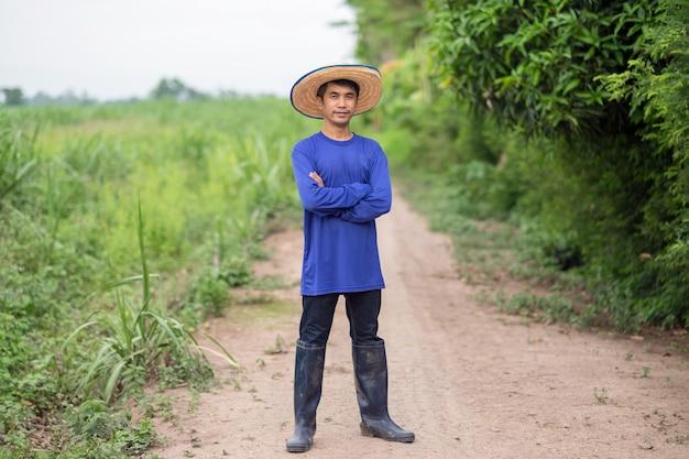 아시아 농부 남자의 전신 서 녹색 농장에서 하늘을보고 손을 교차