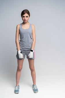 회색 위에 스튜디오에서 연습하는 낚시를 좋아하는 옷과 장갑을 끼고 아름다운 복서 소녀의 전신