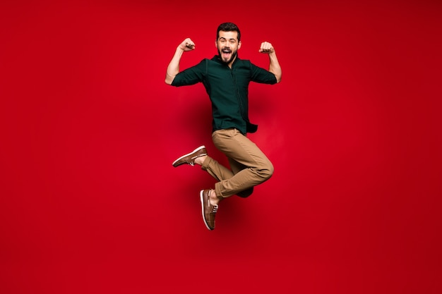 쾌활한 남자 점프의 전신은 그의 힘을 보여줍니다 musclar 손 삼두근 승리 스포츠 콘테스트 비명 느낌 미친 표현 착용 녹색 갈색 셔츠 운동화