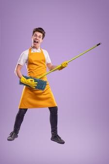 紫色の背景に対して家事中にモップで音楽を演奏するふりをしている黄色のエプロンとラテックス手袋の陽気な若い男性の全身