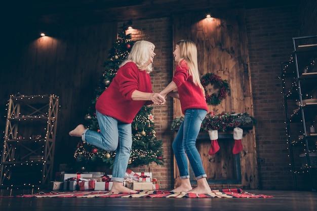 装飾されたロフトスタイルのインテリアハウスで楽しく踊るおばあちゃんの孫の全身