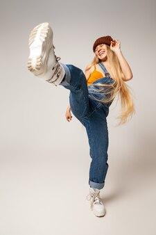 デニムのオーバーオールとトレンディなブーツで幸せなエネルギッシュな女性のヒップスターの全身は、白い背景に対して楽しみながらジャンプして空気を蹴ります