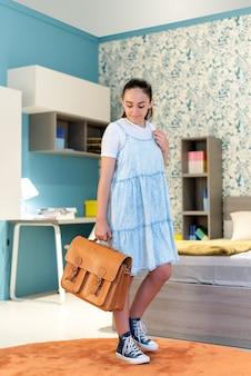 Полное тело позитивной девочки-подростка в повседневной одежде с ретро-школьной сумкой в руке, стоящей в спальне во время подготовки к школьным урокам