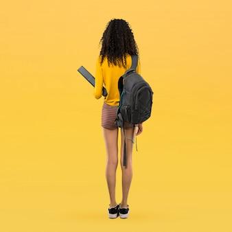 Полное тело подросток студент девушка с вьющимися волосами, оглядываясь назад на желтом фоне