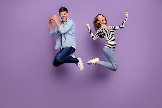 두 사람의 전신 커플 재미 있은 남자 여자 점프 높은 축하 낚시를 좋아하는 경쟁 우승 착용 세련된 캐주얼 복장 절연 파스텔 퍼플 컬러 벽