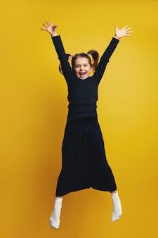 Полное тело молодой милой девушки улыбается и поднимает руки вверх во время прыжка