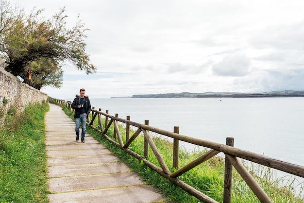 海の上の木製の柵と石の小道を歩くカジュアルな服を着た若い男性旅行者の全身