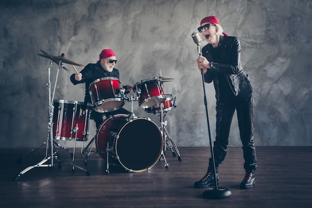 Full body of old lady man rock band perform concert play drum sing