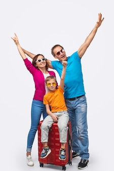 Full body parents and son gesturing with hands while gathering around suitcase before journey against white background
