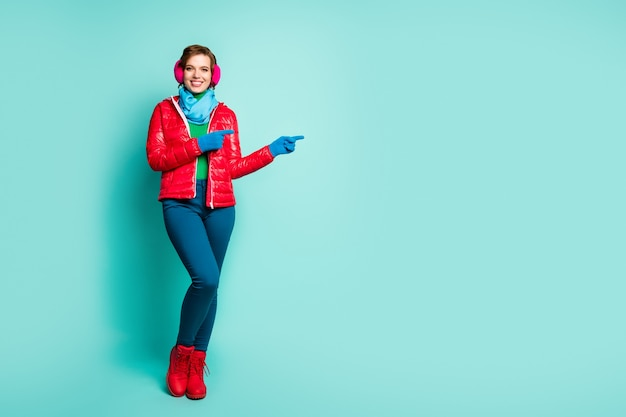 Full body photo of amazing lady directing fingers empty space offer sale prices season shopping wear red overcoat blue scarf pink ear muffs pants boots isolated teal color wall