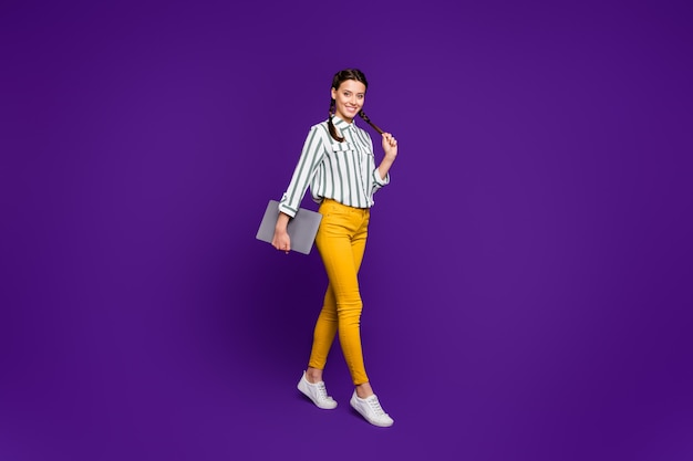 Full body photo of beautiful business lady holding notebook hands walking students lecture class wear striped shirt yellow trousers isolated purple color background